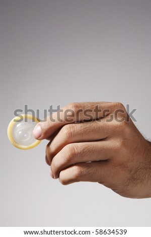 stock image of the man holding condom - stock photo