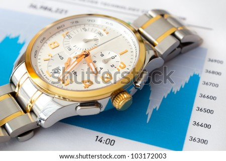 Stock market graph and luxury wristwatch - stock photo