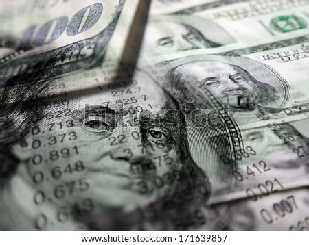 Stock market graphs and money symbolizing investments or investing - stock photo
