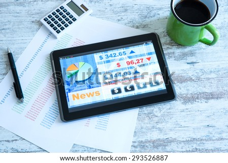 Stock market trading and research software on a Tablet PC on a office Desktop.  - stock photo