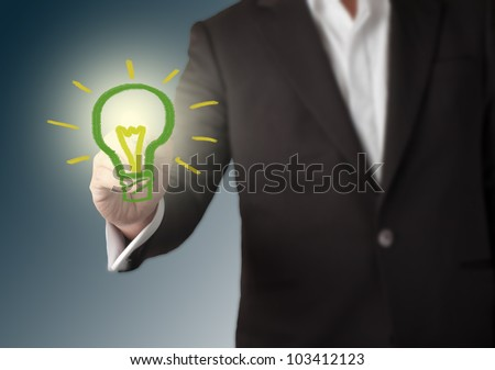 Stock Photo: Businessman with a pen in hand drawing light bulb. Concept for new idea - stock photo