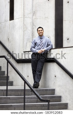 Stock photo of a Hispanic businessman leaning against a wall running alongside a stairwell. - stock photo