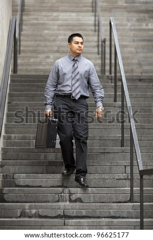 Stock photo of a Hispanic businessman walking down a staircase in a business district, carrying a briefcase. - stock photo