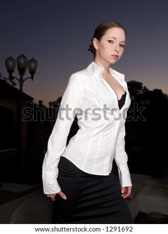 Stock photo of a sexy woman looking intensely at the camera against a dusky background. - stock photo