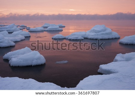 Stock photo of freezing sea at sunset, with vapor above horizon and fresh white snow covering ground. Photographed at North coast of Estonia, Baltic Sea. - stock photo
