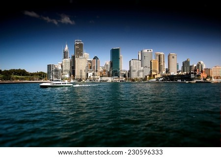 Stock Photo of Sydney CBD from Sydney Harbour featuring the city, circular quays, the rocks, ferry and waterfront skyline. Modern and heavily polarised. - stock photo