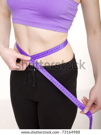 stock photo woman measuring her slim body isolated on white background - stock photo