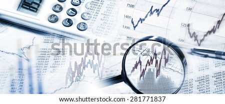 Stock Quotes as graphs and tables with magnifier and calculator in panoramic format - stock photo