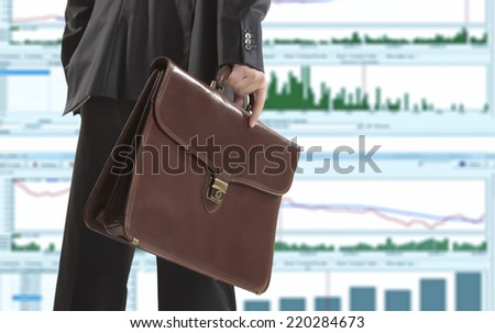 Stock trader with a briefcase looking at monitors - stock photo