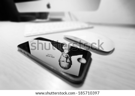 STOCKHOLM - APRIL 6: Mac with reflection of Steve Jobs in a iPhone 5 on table in room in black and white. April 6, 2014 in Stockholm, Sweden. Steve Jobs 1955-2011 - stock photo