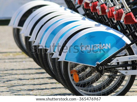 STOCKHOLM - AUG 23, 2015: Lots of identical bicycle wheels on parked bicycles for hire in Stockholm, Sweden, 2015 - stock photo