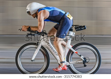 STOCKHOLM - AUG 23, 2015: Male triathlete in aerodynamic equipment cycling into a tunnel with motion blur of the panning at the ITU World Triathlon event in Stockholm. - stock photo