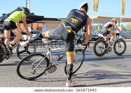 STOCKHOLM - AUG 23, 2015: Men and women  jumping up on professional bicycle racers, wearing advanced helmets in the triathlon transition zone at ITU World Triathlon event in Stockholm, 2015 - stock photo