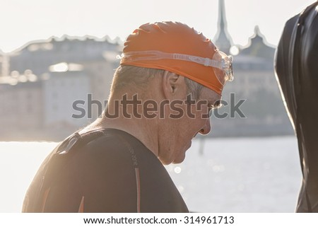 STOCKHOLM - AUG 23, 2015: Older man entering the jetty for the start in early morning at ITU World Triathlon event in Stockholm. - stock photo