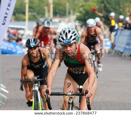 STOCKHOLM - AUG 23: Santos (POR) and Hewitt (NZL) cycling after the transition zone in the Women's ITU World Triathlon series event August 23, 2014 in Stockholm, Sweden - stock photo