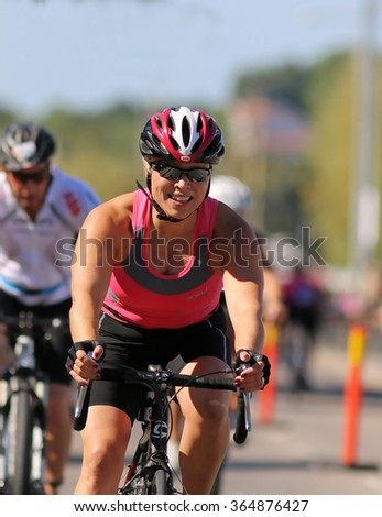 STOCKHOLM - AUG 23, 2015: Smiling, cycling woman wearing pink tank-top followed by de-focused competitors at ITU World Triathlon event in Stockholm, 2015 - stock photo