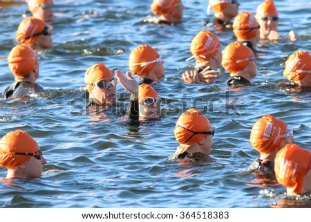 STOCKHOLM - AUG 23, 2015: Waving triathlete  wearing orange swimming caps waiting for the start in the water at ITU World Triathlon event in Stockholm, 2015 - stock photo