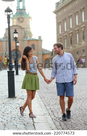 Stockholm couple walking romantic by Royal Palace. Young woman and man holding hands walking in Swedish street in Gamla Stand the old town of Stockholm, Sweden. - stock photo