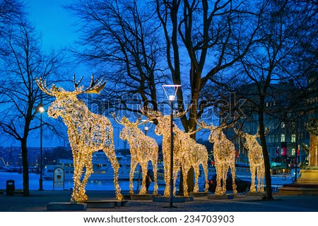 STOCKHOLM - 1 DEC: Group of Mooses made with light at Nybrokajen in Stockholm. 1 December 2014, Sweden. Christmas decoration or installation. - stock photo