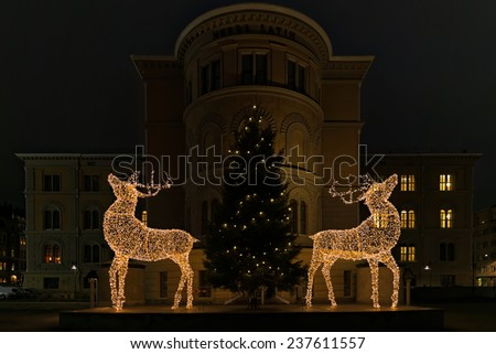 STOCKHOLM - 13 DEC: Two reindeers and a christmas tree with light at Norra Bantorget in Stockholm. 13 December 2014, Sweden. Christmas decoration or installation with a building as a backdrop. - stock photo