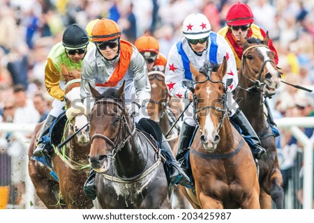 STOCKHOLM - JUNE 6: Closeup of jockeys into last curve at the Nationaldags Galoppen at Gardet. June 6, 2014 in Stockholm, Sweden. - stock photo