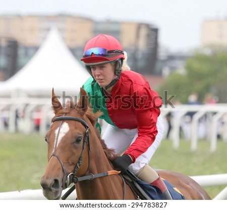 STOCKHOLM - JUNE 06: Female jockey in red, green and white clothes riding a horse race in the horse race at the Nationaldags Galoppen at Gardet. June 6, 2015 in Stockholm - stock photo