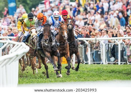 STOCKHOLM - JUNE 6: Jockeys fight to take the lead in the last curve at the Nationaldags Galoppen at Gardet with the crowd behind. June 6, 2014 in Stockholm, Sweden. - stock photo