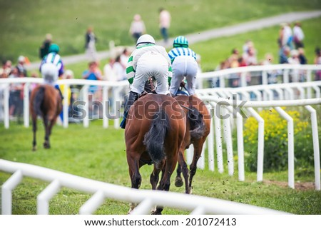 STOCKHOLM - JUNE 6: Riders passing by and into a curve at the Nationaldags Galoppen in Gardet. June 6, 2014 in Stockholm, Sweden. - stock photo