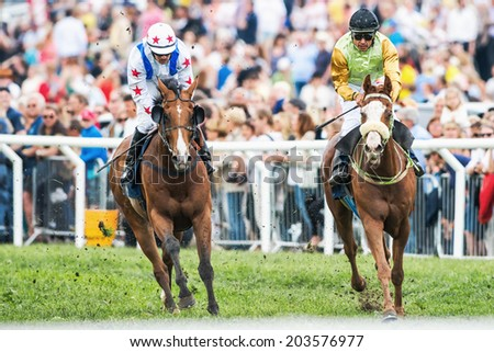 STOCKHOLM - JUNE 6: Two jockeys into last curve at the Nationaldags Galoppen in Gardet. June 6, 2014 in Stockholm, Sweden. - stock photo