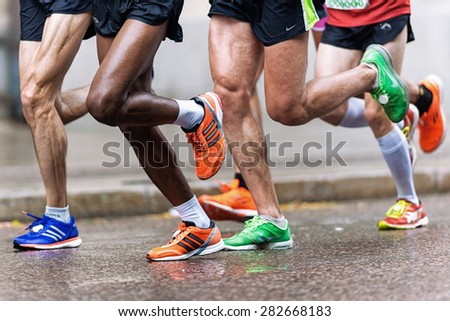 STOCKHOLM - MAY 30: Group of runners with colorful shoes and muscular legs at ASICS Stockholm Marathon 2015. May 30, 2015 in Stockholm, Sweden. The winner Yekeber Bayabel has nr 102. - stock photo