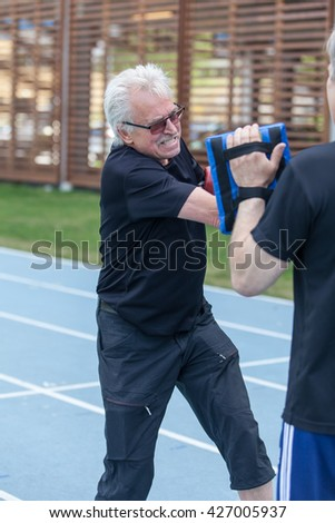STOCKHOLM, MAY 2016, older, grey haired man doing a boxing class outdoors.  - stock photo