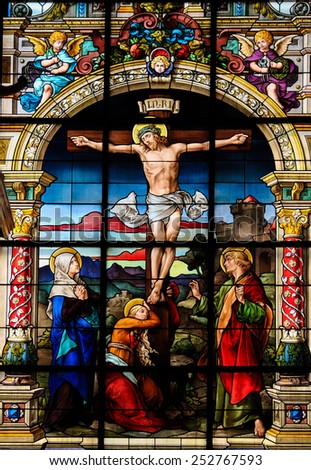 STOCKHOLM, SWEDEN - APRIL 16, 2010:  Beautiful stained glass window created by F. Zettler (1878-1911) at the German Church in Stockholm, depicting Jesus on the Cross on Good Friday. - stock photo