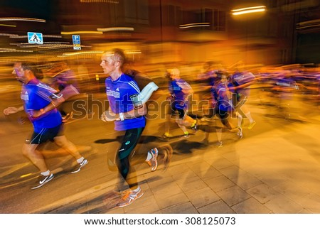 STOCKHOLM, SWEDEN - AUGUST 15, 2015: Male runners in motion blur and colorful light trails at Midnattsloppet or the Midnight run. The track is 10 km and goes thru the streets of Stockholm. - stock photo