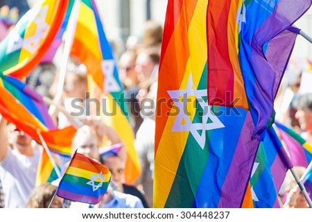 STOCKHOLM, SWEDEN - AUGUST 1, 2015: Rainbow flags with the jewish star of David at the Pride parade in Stockholm. Approx 400.000 spectators at the streets. - stock photo