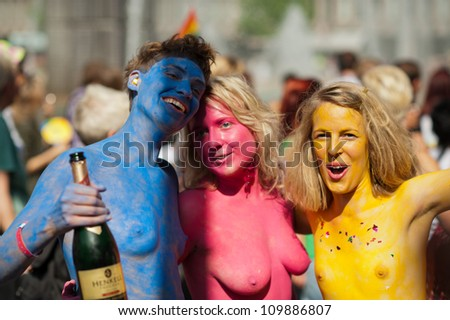 STOCKHOLM, SWEDEN - AUGUST 4: Three cheerful nude painted ladies at Stockholm Pride Parade on August 4, 2012 in Stockholm which attracts an estimated 50000 participants and 500000 spectators. - stock photo