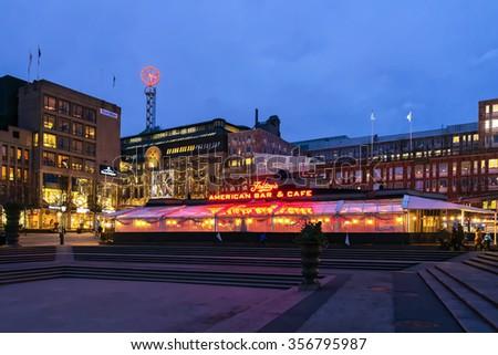 STOCKHOLM, SWEDEN - DEC 27, 2015: Restaurant TGI Fridays at Kungstradgarden with NK in background. - stock photo