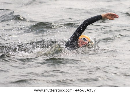STOCKHOLM, SWEDEN - JULY 02, 2016: Laura Lindemann (GER) doing a warmup crawl in the water before the start at Women ITU Triathlon event in Stockholm. - stock photo