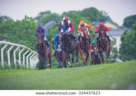 STOCKHOLM, SWEDEN - JUN 6, 2015: Horses with jockeys out of a curve in fast pace at Nationaldagsgaloppen at Gardet. Filters applied - stock photo