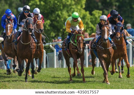STOCKHOLM, SWEDEN - JUNE 6, 2016: Group of jockeys and race horses out of a curve at the Nationaldags Galoppen at Gardet with lush forest behind. - stock photo
