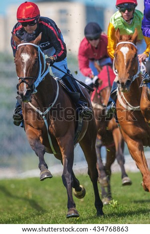STOCKHOLM, SWEDEN - JUNE 6, 2016: Jockeys into a curve at the Nationaldags Galoppen at Gardet with buildings behind. - stock photo