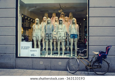 STOCKHOLM, SWEDEN - MAY 26, 2015: City showcase of a clothing store, that display dummy girls in the white dresses at the shopping street of Stockholm, Sweden - stock photo