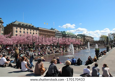 STOCKHOLM, SWEDEN - May 7: People relaxing in the sun by a pond and blossoming cherry trees in central Stockholm, shown on May 7, 2013 in Stockholm.  - stock photo