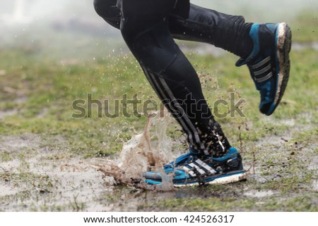 STOCKHOLM, SWEDEN - MAY 14, 2016 Tough Viking around Stockholm Stadion with the water and fire obstacle and closeup of muddy running shoes. - stock photo