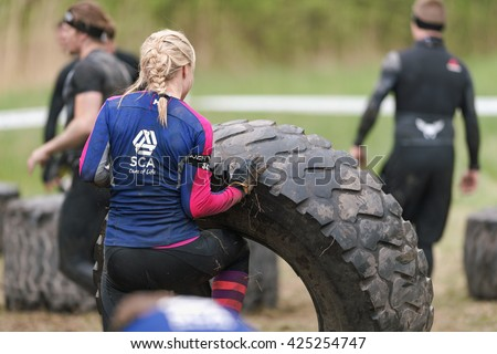 STOCKHOLM, SWEDEN - MAY 14, 2016 Woman flipping tires at Tough Viking obstacle course around Stockholm. - stock photo