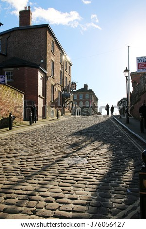 STOCKPORT, UK - FEBRUARY, 10 2016: Shadows on a cobbled street. Stockport is a large town in Greater Manchester and was also at the centre of the country's hatting industry in the 19th century - stock photo