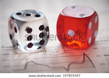 Stocks and shares Trading. Coloured dice on top of the financial section of a newspaper. - stock photo