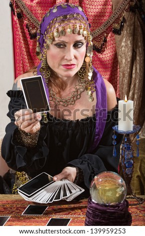 Stoic Roma lady looking at a tarot card indoors - stock photo