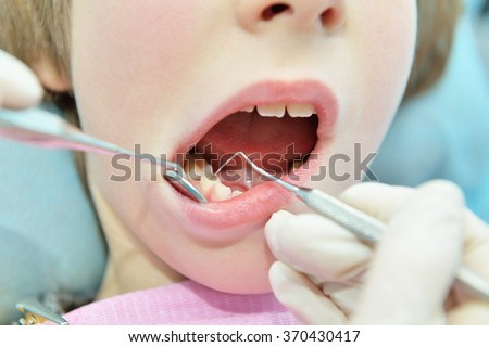 Stomatologist. Dental health. Female dentist curing a child patient in doctor's consulting room. Pediatric dentist. Medical inspection. Health care.  - stock photo