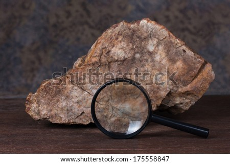stone and magnifying glass on wood table. - stock photo
