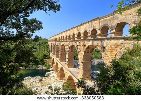 Stone aqueduct of Pont du Gard surrounded by vegetation near Nimes, France - stock photo